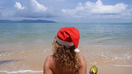 Woman on the Beach in Santa Hat. Christmas and New Year