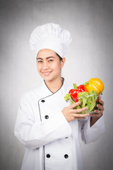 Woman chef holding bowl of fresh vegetables