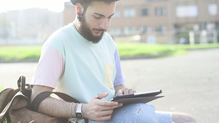 young handsome hipster bearded man using technological device