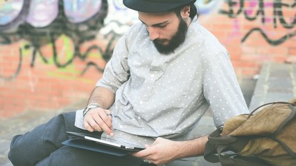 young bearded hipster man using tablet in the city