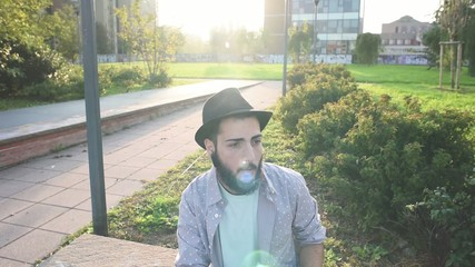 young handsome bearded hipster man smoking in the city