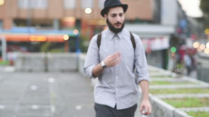 young handsome bearded hipster man walking in the city