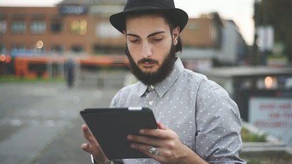 young hipster man using tablet by night in the city