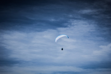 Paraglider soaring in the stormy sky