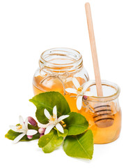 Honey in glass jars and flowers of lemon