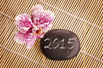 2015, pink phalaenopsis orchid and pebble on a bamboo mat