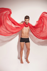 man fluttering a red textile while looking at the camera
