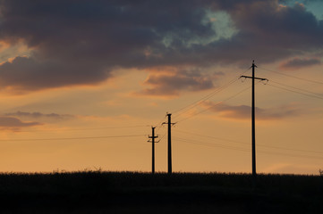sunset and three electric pylons
