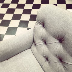 Armchair on black and white tile background