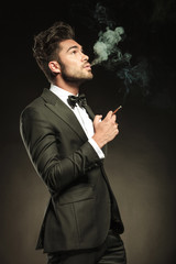 young business man blowing smoke while holding a cigarette