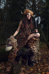 The ancient woman in the forest with an ax in his hand.