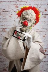 Sad clown makes selfie on cellphone.
