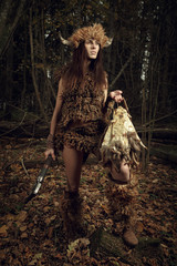 Ancient woman hunter in the forest with an ax in his hand. Histo