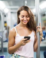 Woman using smartphone in subway