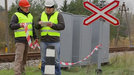 Railway engineer with tablet PC and worker with warning tape