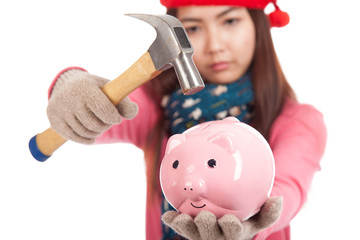 Asian girl with red christmas hat ,hammer and piggy bank