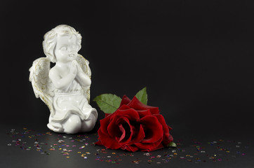 Ornamental angel with red rose for gifts, isolated on black