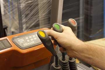 Male hand controlling forklift truck lever