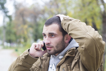 Young  worried man talking on phone