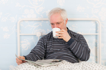 Senior man reading newspapers in bed