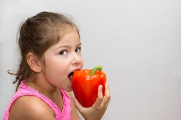 Mädchen beisst in Paprika