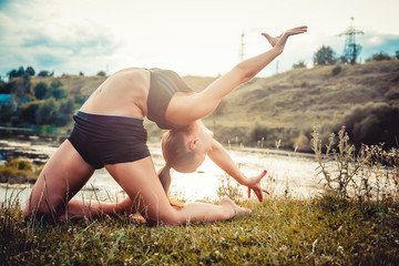 Sports girl doing exercises on the banks of rivers