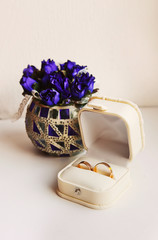 Wedding rings in a box on the flowers background