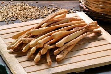 Grissinis, palillos de pan en ambiente rústico.