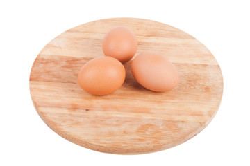 Three eggs on a wooden board isolated on white background
