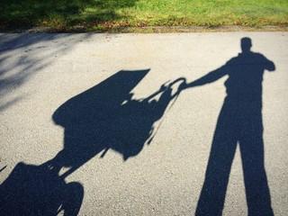 Schattenmann mit Kinderwagen beim Spazieren