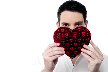 Handsome man holding heart shape gift box