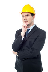 Thoughtful architect wearing a hard hat