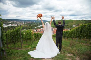 Junges Brautpaar jubelt und freut sich in den Weinbergen