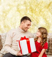 smiling father and daughter with gift box