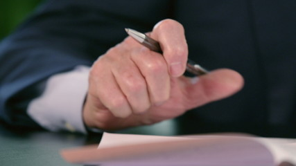 Hand of a business man signing documents with pen