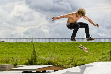 boy doing skateboard trick in skate park