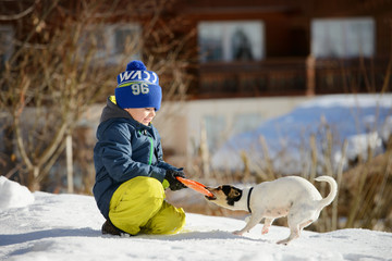A little boy is playing with a dog on the snow outside