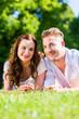 canvas print picture - Paar liegt in Sonne auf Park Wiese