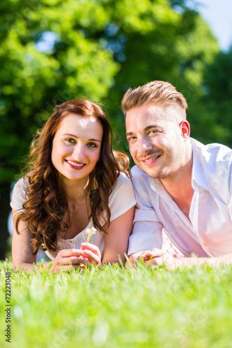 canvas print picture Paar liegt in Sonne auf Park Wiese