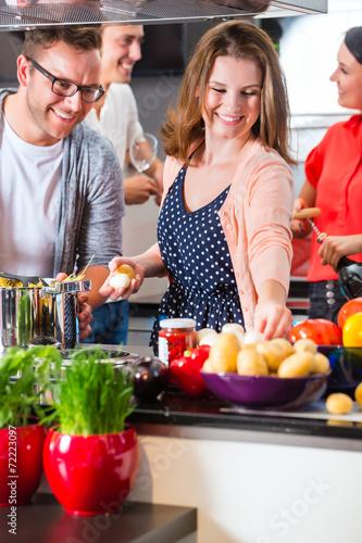 Freunde kochen Pasta und Fleisch zuhause in Küche - 72223097