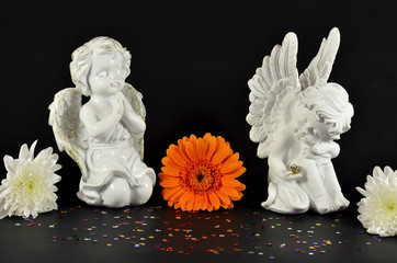 Christmas angels with flowers for gifts, isolated on black