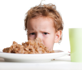 Dissatisfied girl with a big bowl of porridge