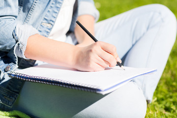 close up of girl with notebook writing in park