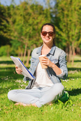 smiling young girl with notebook and coffee cup