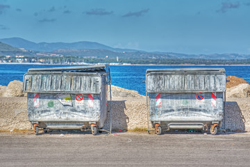 metal trash containers by the shore