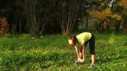 Girl doing exercise in autumn park