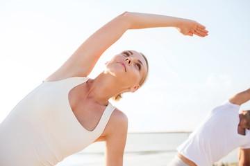 close up of couple making yoga exercises outdoors