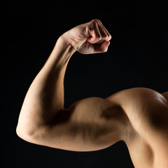 close up of young man showing biceps