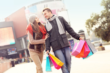 Joyful couple shopping in the city
