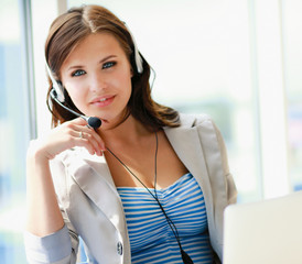 businesswoman talking on the phone while working on her computer